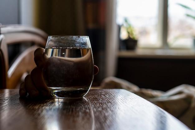 Mann ruht sich im bett aus und bekommt ein glas wasser. durst konzept b