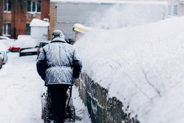Mann säubert den yard, der schneefräse entfernt