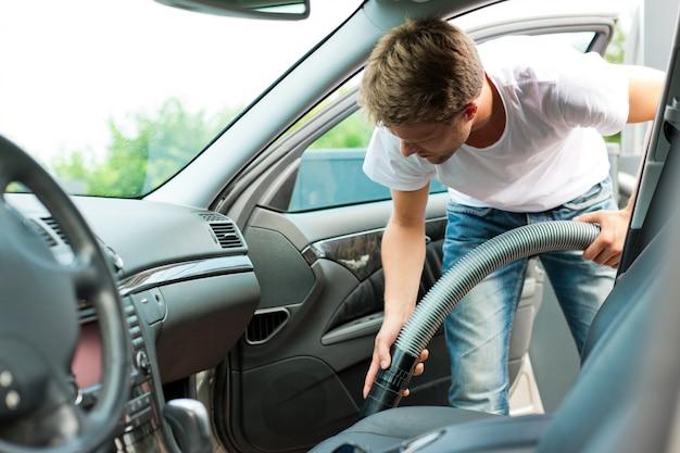 Mann saugt oder säubert das auto