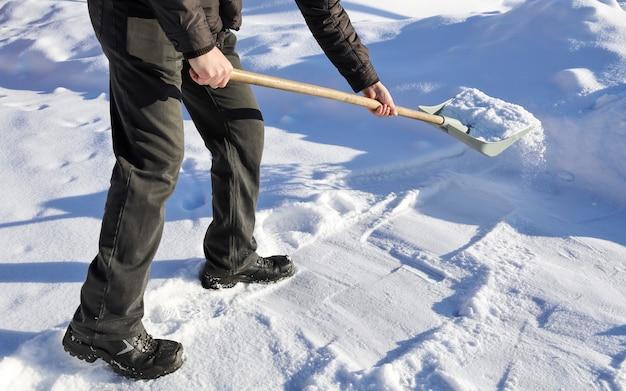 Mann schaufelt schnee, hebt und wirft am wintertag Premium Fotos
