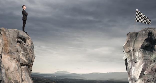 Mann schaut auf eine flagge auf der anderen seite des berges. geschäftskonzept des geschäftsmannes überwinden die probleme