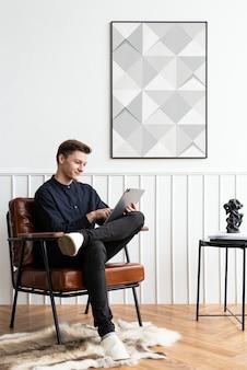 Mann schaut auf sein tablet in seinem wohnzimmer