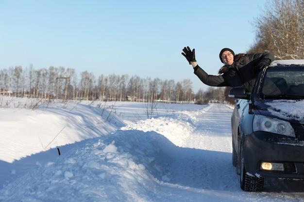 Mann schaut aus dem autofenster auf die schneebedeckte straße und lächelt