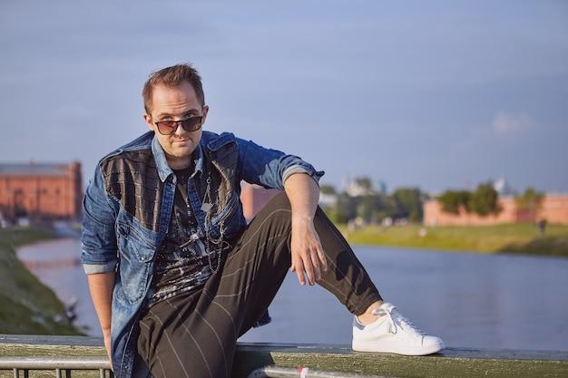 Mann schaut durch sonnenbrille heraus, während er auf dem geländer der brücke sitzt.