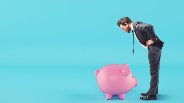 Mann schaut in das sparschwein und sucht nach geld
