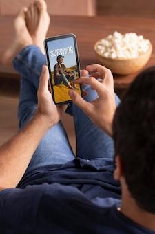 Mann schaut netflix auf seinem smartphone