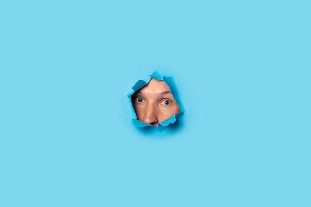 Mann schaut raus und schaut aus dem loch auf blau