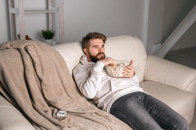 Mann schaut sich filme an, die zu hause auf einer couch liegen