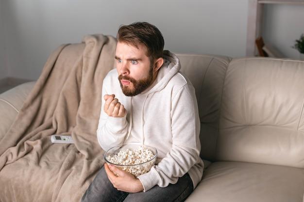 Mann schaut sich filme an, die zu hause auf einer couch sitzen