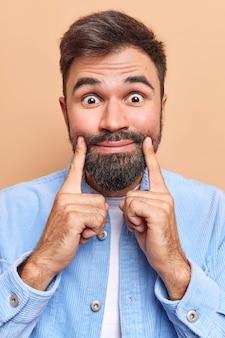 Mann schaut überraschend in die kamera und hält zeigefinger in der nähe der lippenecken, zwingt zum lächeln, gekleidet in blauem samthemd, isoliert auf braun