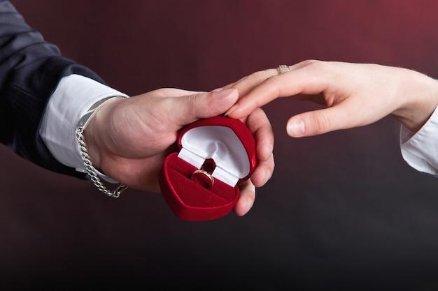 Mann schenkt frau einen goldenen verlobungsring in einer roten schachtel