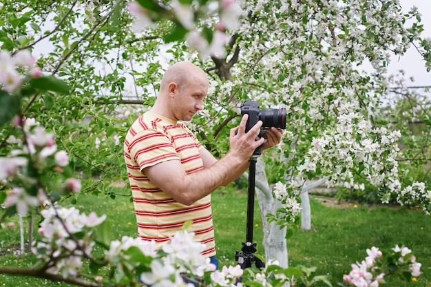 Mann schießen auf die kamera in einem blühenden frühlingsgarten