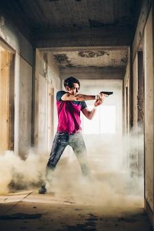 Mann schießt mit einer waffe in einem zerstörten gebäude in einem dampf