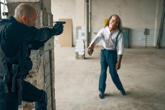 Mann schießt zombie, albtraum in verlassener fabrik, kugeleffekt. horror in der stadt, gruselige krabbeltiere, weltuntergangs-apokalypse, verdammtes böses monster