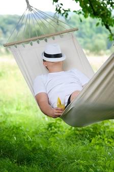 Mann schläft auf hängematte