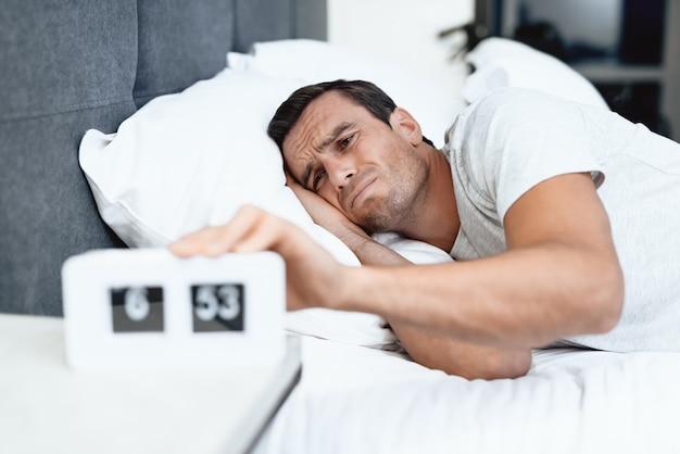 Mann schläft in seinem weißen bett