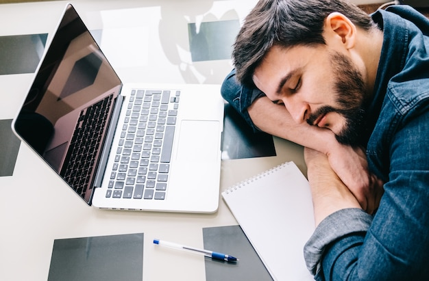 Mann schläft mit seinem laptop