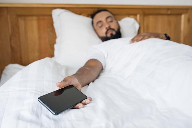 Mann schläft, nachdem er zeit mit seinem telefon verbracht hat
