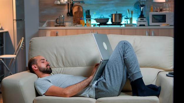 Mann schläft vor dem fernseher ein, während er am laptop arbeitet
