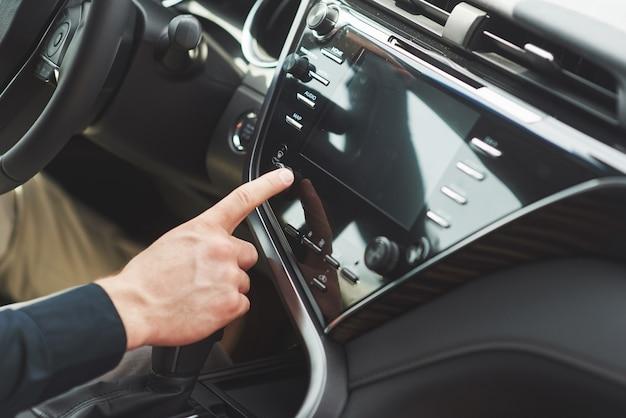 Mann schließt ein audiosystem in das auto ein.