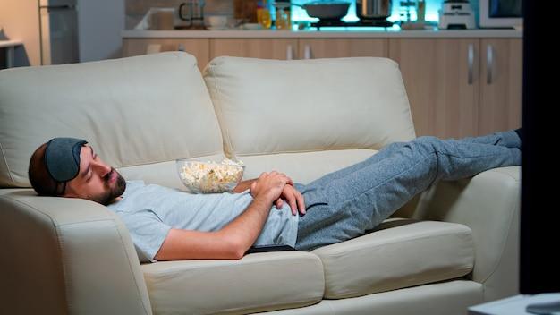 Mann schließt sein auge und schläft auf der couch im wohnzimmer ein