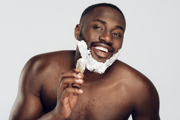 Mann schmiert rasierschaum auf gesicht durch rasierpinsel.