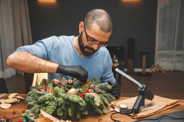 Mann schmückt einen weihnachtskranz neujahr urlaub dekoration weihnachtsbaum kranz dekoration diy