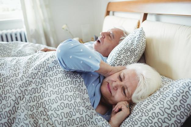 Mann schnarcht und frau bedeckt ihre ohren, während auf bett schlafen
