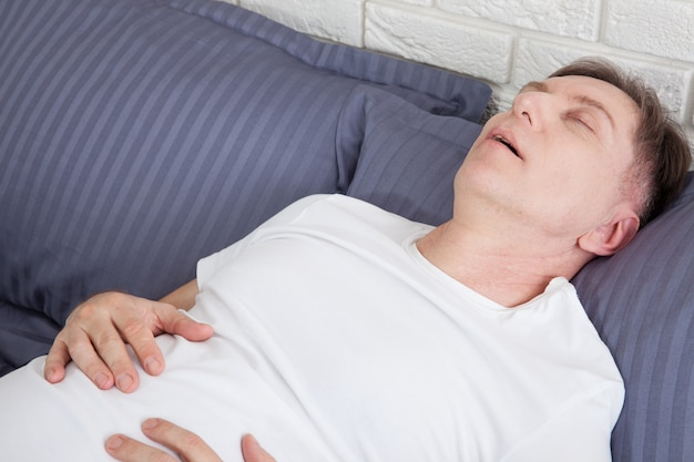 Mann schnarcht wegen schlafapnoe, die im bett liegt.