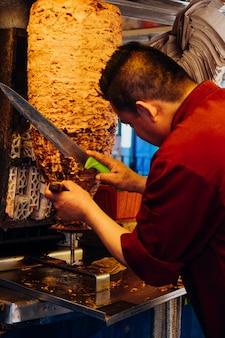 Mann schneidet ein stück fleisch in einem kreisel für tacos al pastor, typisch mexikanisches gericht.