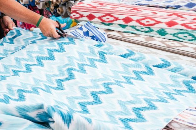 Mann schneidet einen rest aus einer stoffrolle. llengües mallorquines