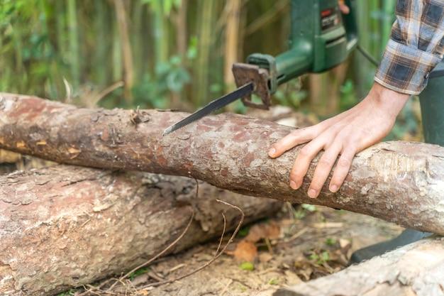 Mann schneidet mit elektrischer säge staub und bewegungen holzfäller sägt baum mit kettensäge auf sägewerk