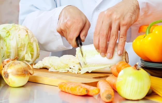 Mann schneidet salat
