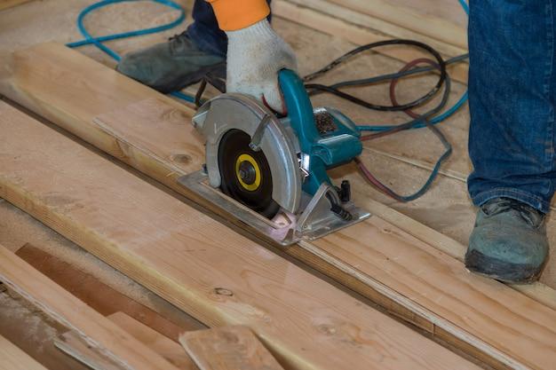 Mann schneidet sperrholz mit einer elektrischen kettensäge mit professionellen werkzeugen
