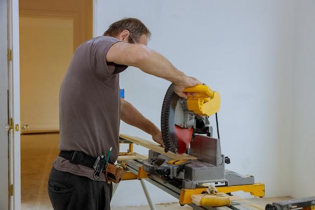 Mann schnitt das hölzerne formteil mit kreissäge, baubauindustrie