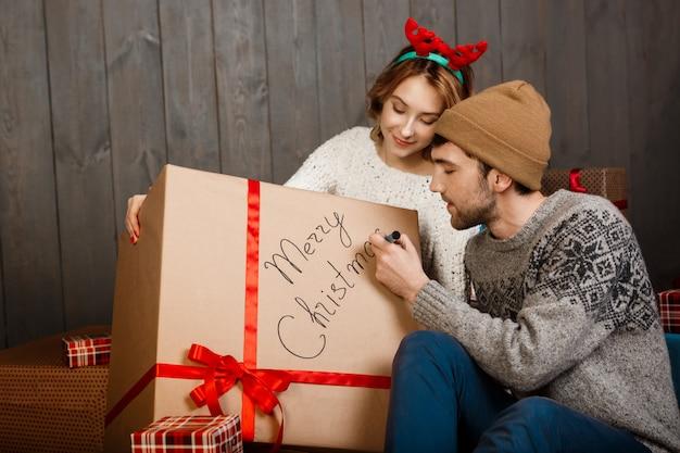 Mann schreibt auf geschenkbox frohe weihnachten, die mit freundin sitzen.