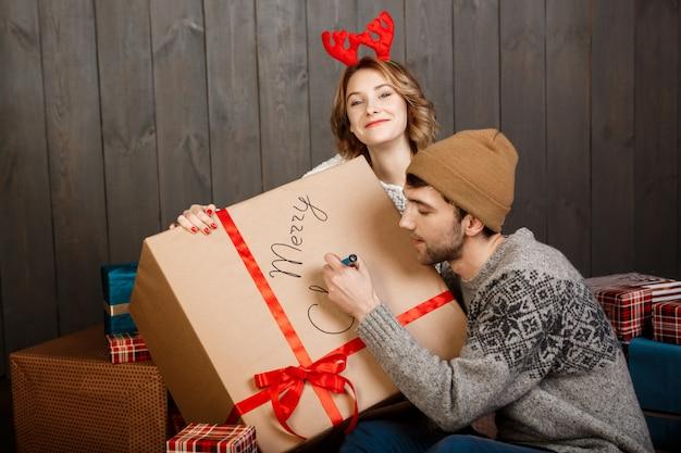 Mann schreibt auf geschenkbox frohe weihnachten, die mit freundin sitzen