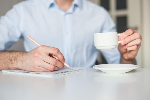 Mann schreibt aufgabenliste in notizbuch und arbeitet zu hause. kaffee trinken, bleistift behalten