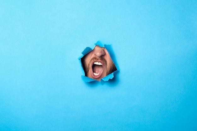 Mann schreit aus einem loch auf blau