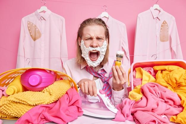 Mann schreit laut, hält den mund geöffnet rasiert und bügelt kleidung gleichzeitig umgeben von wäschestapeln in körben, die die tägliche hausarbeit und die hausarbeit satt haben
