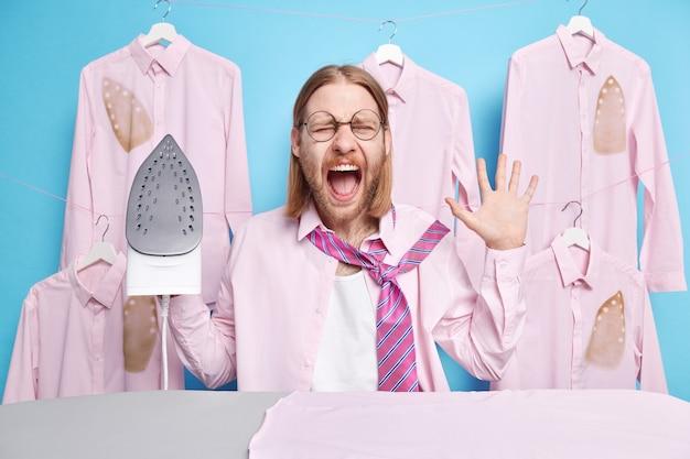 Mann schreit laut hält den mund offen hebt die handfläche hält das bügeleisen hält die kleider für das formelle treffen mit den kollegen posiert in der waschküche laundry