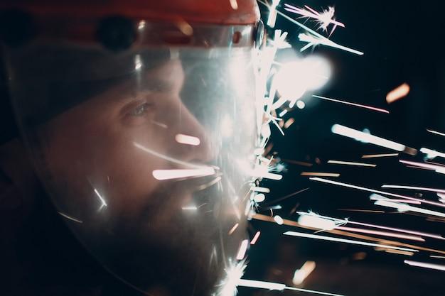 Mann-schweißer-schleifer in transparenter schutzmaske mit funkenflug in der dunkelheit.