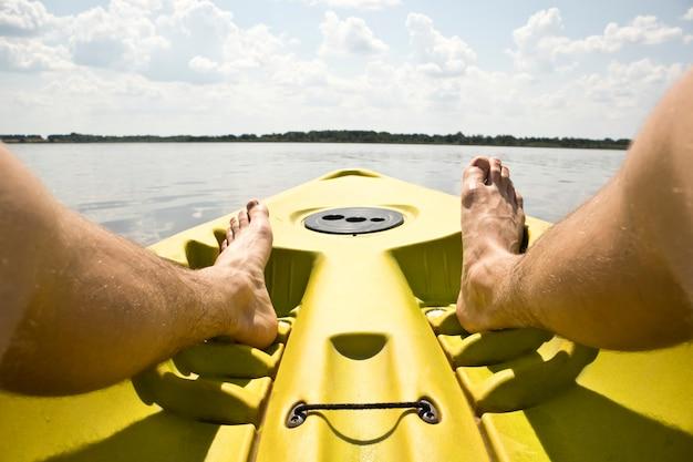 Mann schwimmt auf einem kajak auf dem see