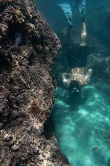 Mann schwimmt unter dem ozean