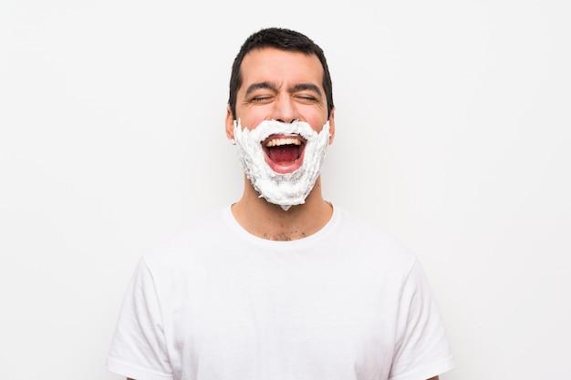 Mann seinen bart rasieren über isolierte weiße wand mit weit offenem mund nach vorne schreien
