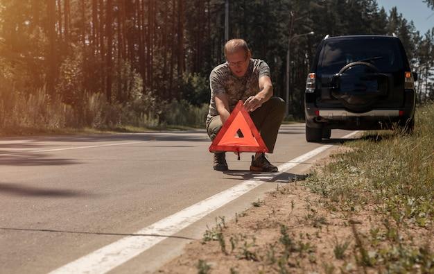 Mann setzt dreieck vorsichtsschild auf straße in der nähe von kaputtem auto