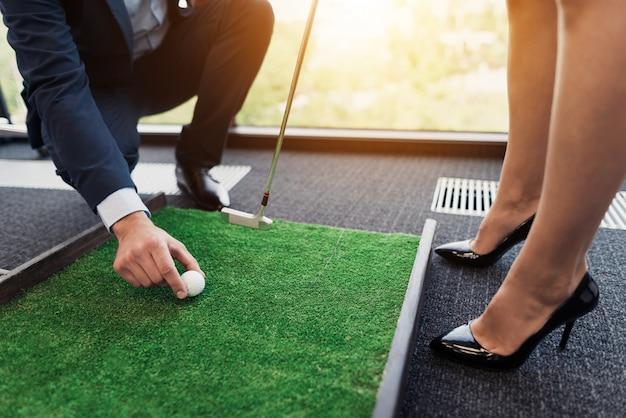 Mann setzt golfball vor geschäftsdame in strengen anzug ein