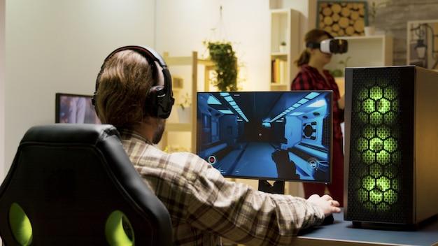 Mann setzt kopfhörer auf und fängt an, videospiele auf dem computer zu spielen. frau, die virtuelle realität mit vr-headset im hintergrund erlebt.
