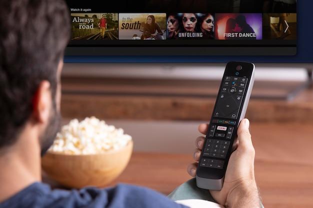 Mann sieht sich eine show im fernseher an