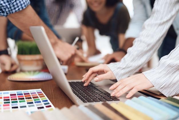 Mann sitzt am laptop. er arbeitet in einem kreativbüro.